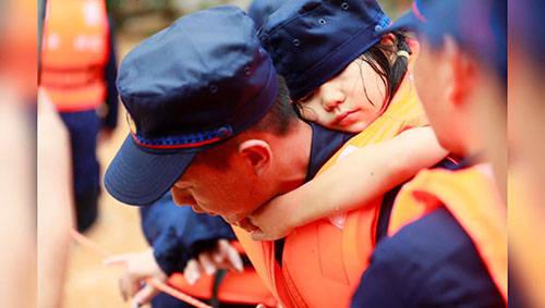 被洪水围困女孩趴消防员背上睡着
