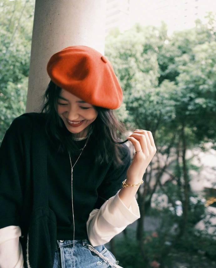刘雯戴红色贝雷帽灵动可爱挎黑布袋简约时尚